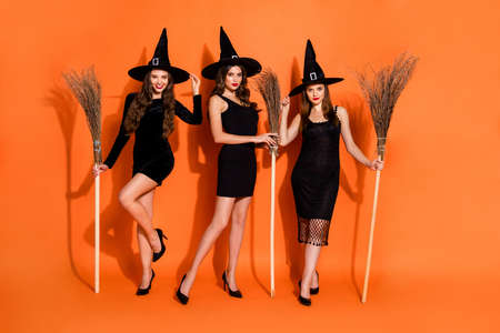 Full body photo of three cruel witch ladies holding brooms cant wait begin night flight wear black mini dresses and wizard hats isolated orange color background
