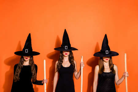 Photo of three cruel witch ladies holding brooms not showing evil facial expression wear black dresses and wizard hats isolated orange color background 写真素材 - 130723921