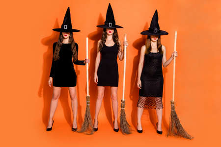 Full body photo of three cruel witch ladies holding brooms not showing evil facial expression wear black dresses and wizard hats isolated orange color background