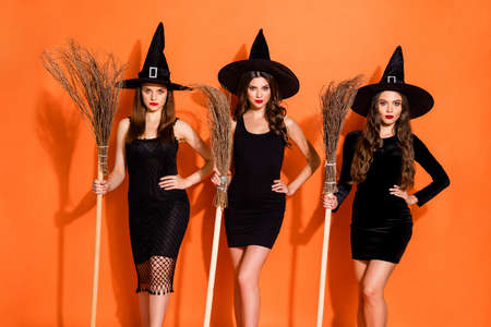 Photo of three cruel witch ladies holding brooms in hands waiting full moon for flying wear black dresses and wizard hats isolated orange color background 写真素材 - 130723926