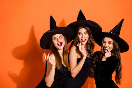 Photo of three cruel witch ladies calling handsome guys using paranormal magic powers wear black dresses and wizard hats isolated orange color background