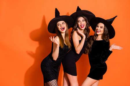 Photo of three cruel witch ladies calling handsome guys using magic powers wear short black dresses and wizard hats isolated orange color background 写真素材