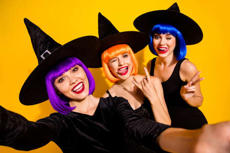 Live video report from disco masquerade. Closeup photo of cheerful cool red lipstick blinking beautiful carefree magic bloggers taking selfie orange blue violet wigs isolated vibrant color background Фото со стока