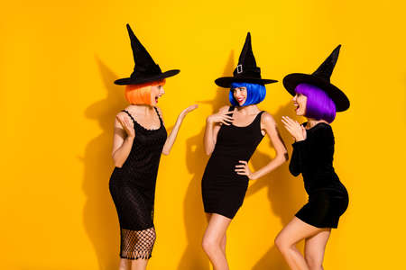 Photo of three excited cunning frightening beautiful ladies discussing new recipe of brew and potion the way how to cook it in a cauldron wearing caps isolated bright color background
