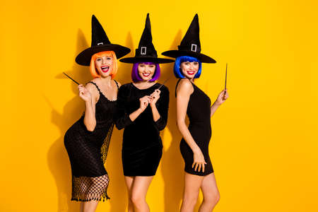 We will tell you horror stories about creatures and demons concept. Photo of three beautiful wearing dark outfit caps ladies holding using wands isolated bright color background