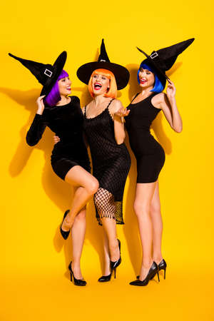 Do not listen to conversation between witches concept they can send a curse. Vertical full body photo of excited beautiful attractive spooky in caps ladies having fun time isolated vivid background