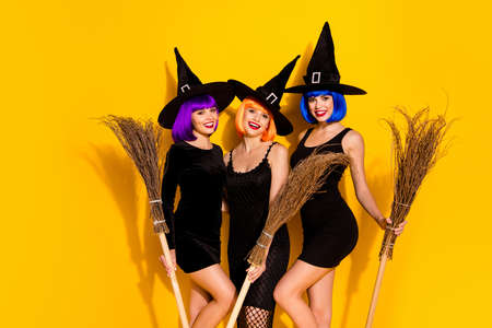 Photo of three in orange blue violet color dyed hairstyle magicians sorcerers conjurers enchants ready for making brew in cauldron holding brooms isolated vivid color background