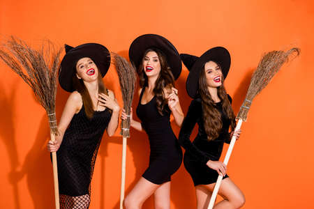 Photo of three cruel witch ladies holding brooms waiting full moon laughing out loud wear black mini dresses and wizard hats isolated orange color background