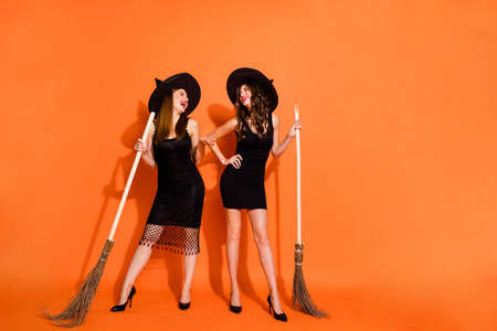 Photo of two cruel witch ladies holding brooms evil laughing wear black dresses and wizard hats isolated orange color background
