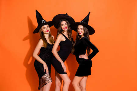 Photo of three cruel witch ladies ready for halloween student party wear teasing black short mini dresses and wizard hats isolated orange color background 写真素材