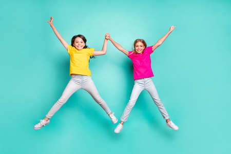 Full length body size photo of two nice cute beautiful people girls jumping, like stars while isolated with teal background