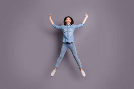 Full length photo of crazy lady jumping high in star shape celebrating, summer holidays beginning wear casual jeans outfit isolated grey background