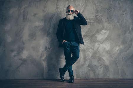 Photo pleine grandeur d'un homme masculin dur et attrayant avec des lunettes de vue debout près du mur regardant porter des chaussures de pantalon de veste de manteau isolées sur fond gris