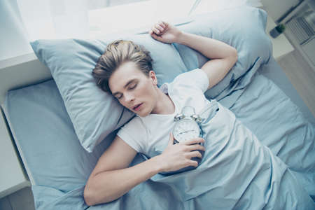 Top high above angle photo of overworked blonde haired man lying on bed sleep ignore alarm clock ring bell missed first class in college stay in house indoors