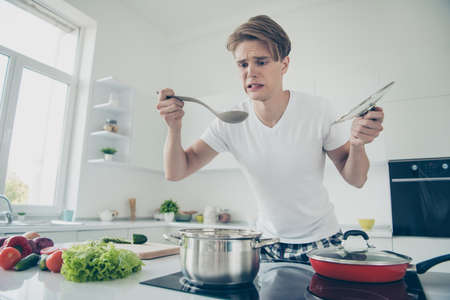 Portrait of his he nice attractive cute dissatisfied upset guy making dinner lunch tasting bad bouillon at light white modern style interior house indoors Фото со стока