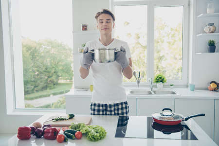 Portrait of his he nice attractive cute dreamy guy housekeeper smelling aromatic useful bouillon making snack lunch at light white modern style interior house hotel indoors