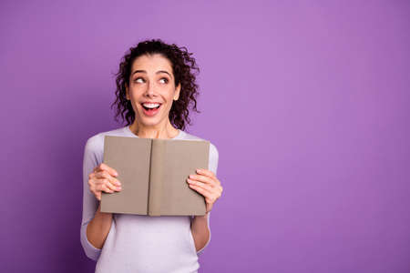 Photo of curly wavy charming cute nice lady impressed after reading her paper book excited ecstatic smiling toothily isolated over purple pastel color background Banco de Imagens