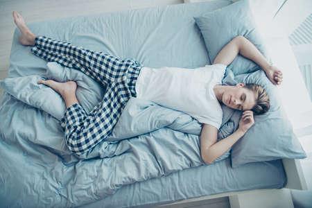 Boven boven hoge foto van dromerige rustige man liggend op bed slapend op linnen zijn rug dromen genieten van weekenden vrije tijd dragen geruite pyjama binnenshuis