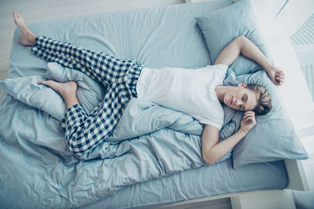 Top above high photo of dreamy calm man lying on bed sleeping on linen his back have dreams enjoy weekends free time wear checkered pajama in house indoors