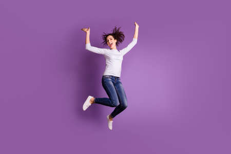 Full length body size photo of charming overjoyed jumping recjoicing girlfriend wearing jeans denim footwear ecstatic isolated over purple pastel color background