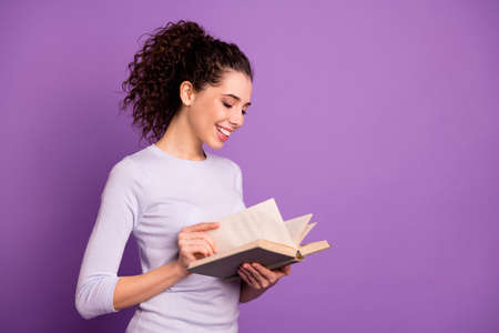Photo of sweet cute girlfriend leafing through her book to learn new information holding hands isolated over purple pastel color background Imagens - 131080472