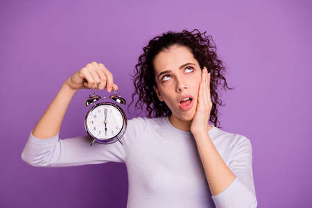 Photo of white cute nice curly wavy stylish funny cheerful woman bothered with her alarm clocks ringing holding it with hand grimacing isolated over purple pastel color background