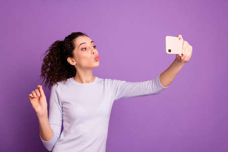 Photo of cheerful curly wavy stylish trendy lovely sweet millennial girl kissing her new telephone wearing sweater holding hair isolated over violet pastel color background