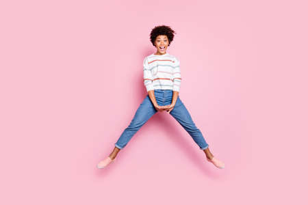 Full length body size photo of cute nice charming black woman jumping up doing splits with hands folded expressing joyfulness with face in jeans denim sweater isolated over pink pastel color background Banco de Imagens