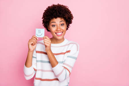 Photo of cheerful charming cute nice girlfriend black skinned holding piece of paper with emoji drawed on wearing white striped sweater isolated over pastel pink color background
