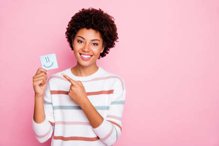 Photo of pretty dark curly skin lady holding in hands little paper emoticon directing finger what mood is better wear white striped pullover isolated pastel pink color background 版權商用圖片
