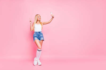 Full size photo of funky positive girl blogger take selfie make v-signs wear stylish outfit white tank-top isolated over pastel color background