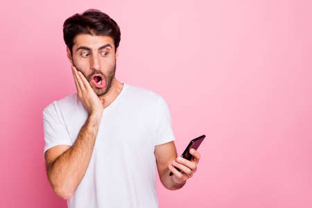 Portrait of funky shocked handsome middle eastern man use hold cellphone look read information get terrible feedback dislike impressed scream omg wear style clothes isolated pink color background