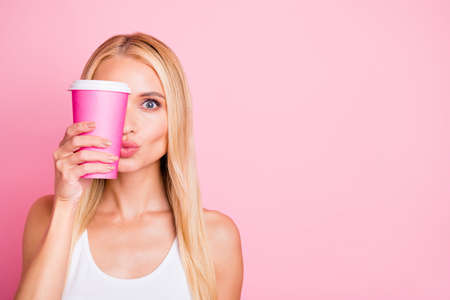 Photo of pretty lady holding hot beverage takeout container hiding half facial expression wear casual outfit isolated pink color background Stock fotó
