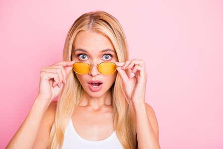 No puede ser real. Foto de dama bonita con la boca abierta, no creo que los ojos usen especificaciones para el sol y traje casual aislado de fondo de color rosa