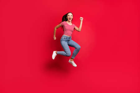 Full length body size trendy photo of crazy winning victorious girl wearing jeans denim crazily running towards shopping mall while isolated with red background