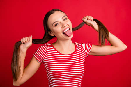Close up photo of excited cheerful nice funny girlfriend wearing striped t-shirt while isolated with red background