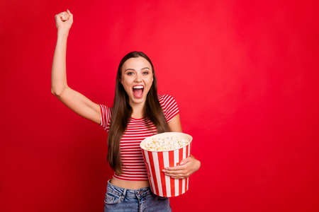 Photo of rejoicing trendy excited overjoyed beautiful girlfriend happy that her favorite sport team won wearing jeans denim while isolated with red background Stock Photo
