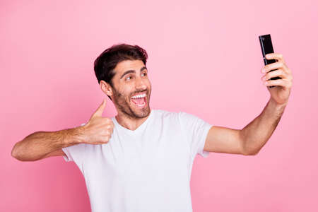 Portrait of funny funky crazy cheerful middle eastern man blogger on summer holidays recommend his vacation take selfie show thumb up wear stylish trendy white t-shirt isolated pink color background