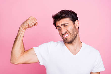 Portrait of funny funky disappointed middle eastern man show his muscles look dislike new sportive gym fitness body building workout wear white t-shirt isolated over pastel color background