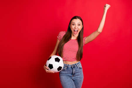 Photo of cute nice cheerful excited funny ecstatic girlfriend overjoyed with victory of her team while isolated over red background holding ball with hands wearing jeans denim