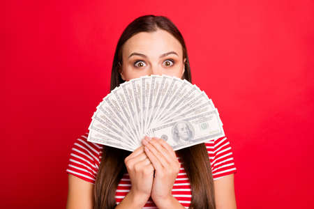 Close up photo of beautiful cute girl wearing striped t-shirt holding money with her hands hiding behind it while isolated with red background