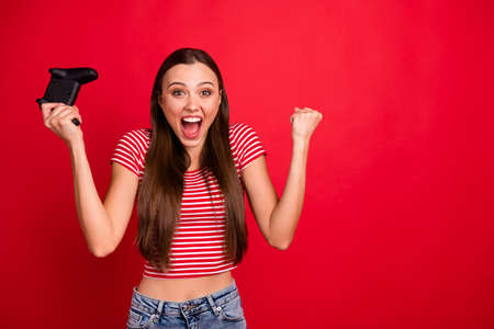Photo of beautiful trendy charming pretty brown haired cute nice lovely girlfriend addicted with video games wearing striped t-shirt while isolated with red background