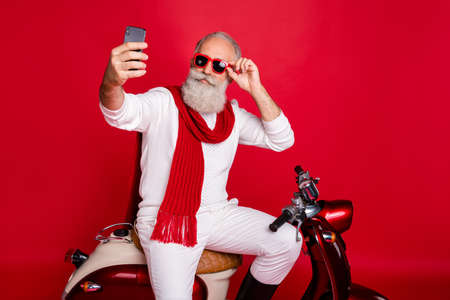 Portrait of his he nice attractive stylish trendy confident cool gray-haired man taking making selfie touching sun specs eyewear eyeglasses isolated over bright vivid shine red background