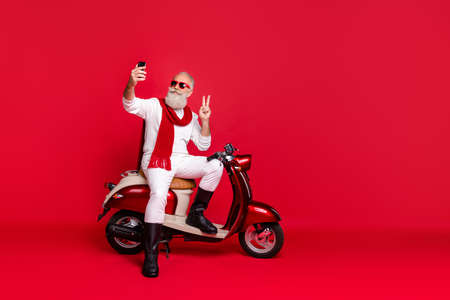 Portrait of his he nice attractive stylish trendy confident content optimistic gray-haired man taking making selfie showing v-sign isolated over bright vivid shine red background