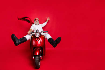 Full size photo of funky grandfather screaming raising his palm riding scooter wearing white sweater trousers pants boots isolated over red background Stok Fotoğraf