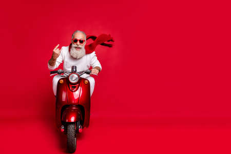 Full length photo of cheerful old man in eyewear eyeglasses showing rocker sign driving his bike wearing white sweater isolated over red background Stock Photo