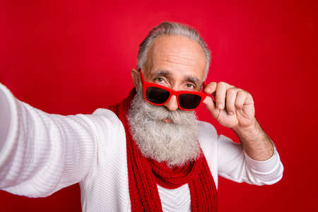 Fancy grey haired santa man making self photos wear sun specs knitted jumper isolated red background