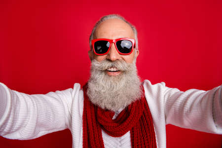 Excited aged santa man making self photos wear sun specs knitted jumper isolated red background 스톡 콘텐츠