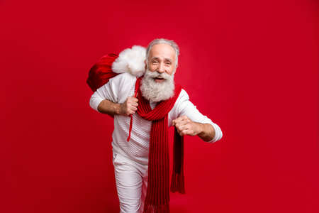 Trendy grey haired man creative santa style came cool party with big bag wear fashion knitted clothes isolated red background