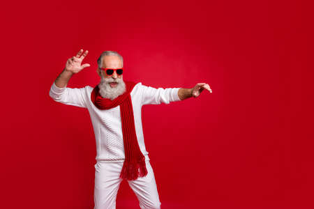 Cool santa character aged man moving like star at exciting party wear sun specs knitted clothes isolated red background Standard-Bild - 131541053